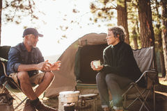 Mature man and woman sitting and talking at a campsite Royalty Free Stock Photography