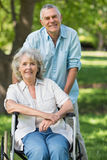 Mature man with woman sitting in wheel chair at park Stock Photos