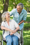 Mature man with woman sitting in wheel chair at park Stock Photography