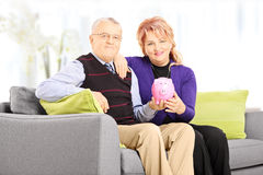 Mature man and woman on sofa holding a piggy bank at home Stock Images