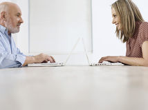 Mature Man And Woman Using Laptops Royalty Free Stock Photos