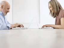 Mature Man And Woman Using Laptops. Side view of a mature man and woman using laptops on table royalty free stock images