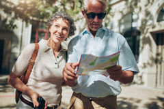 Mature man and woman using  map while sightseeing. Portrait of senior tourist couple in town using a map. Mature men and women using map while sightseeing Royalty Free Stock Photos