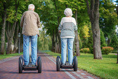 Mature man and woman using modern transport royalty free stock images