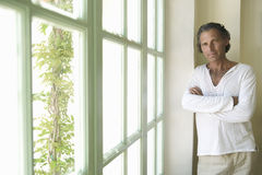 Mature man by wooden window. Stock Photos