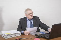 Mature man at work looking at paperwork. Sitting at a desk Stock Image