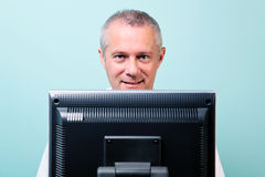 Mature man working at a computer. Looking over the screen stock photo
