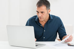 Mature Man Working At The Computer. Portrait Of A Mature Man Looking At Laptop Holding Document royalty free stock image