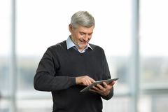 Mature man working on computer tablet. Stock Image