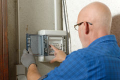 Mature man working with electric box at house Stock Photography