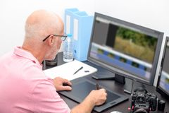 Mature man working with graphics tablet in his office stock image