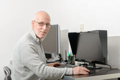 Mature man working with his computer. A mature man working with his computer stock photography