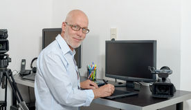 Mature man working with his computer stock image