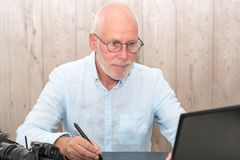 Mature man working on his graphics tablet royalty free stock photo