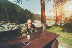 Man with laptop in mountans settings. Mature man is working on his laptop outdoors in nature during his vocation; aged forester using his laptop for e-mail Stock Images