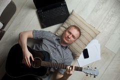 Mature man working at home. Self-employed mature man working at home. Playing the guitar, meditating Royalty Free Stock Image