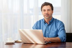 Mature man working at home in the kitchen royalty free stock photography