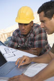 Mature Man Working On Laptop With Co-Worker Royalty Free Stock Photography