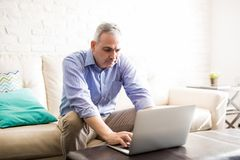 Mature man working on laptop at home. Mature caucasian man sitting on the couch at home and using a laptop computer royalty free stock photography