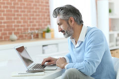 Mature man working on laptop at home Royalty Free Stock Image