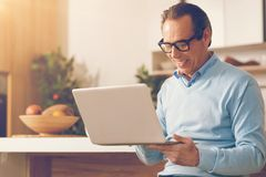 Mature man working on laptop in kitchen. Advanced living. Smiling male adult wearing glasses sitting on a chair and focusing his attention on a screen of a Royalty Free Stock Image