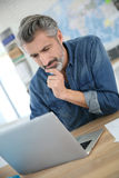 Mature man working on laptop at school Stock Photography