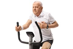 Mature man working out on an exercise bike and having a heart at Stock Image