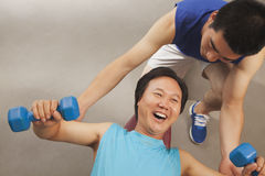 Mature man working out with weights, trainer supporting him, overhead view Stock Images