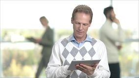 Mature man working on pc tablet. Adult man using digital tablet while standing on office window background. Middle-aged office manager stock video