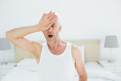 Mature man yawning in bed Stock Images