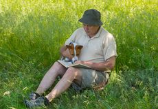 Mature man and young dog reading interesting book. Under tree shadow royalty free stock image