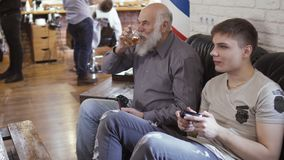 Old and young men waits their turn in barbershop and plays videogame. Mature man with young guy sits on sofa in a hall of barbershop and plays video game. People stock video