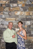 Mature man and young woman standing beside stone wall, holding glasses of white wine, smiling, portrait Royalty Free Stock Images