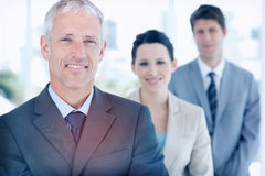 Mature manager followed by two young business people Stock Photo