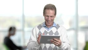 Mature manager talking via pc tablet. Middle-aged caucasian office worker received video call from colleagues on computer tablet, office window background stock video footage