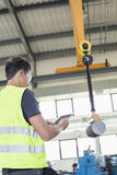 Mature manual worker with digital tablet operating crane to lift steel in industry Royalty Free Stock Photography