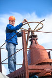 Mature manual worker turning huge valve gate Royalty Free Stock Photography