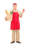 Mature market vendor holding a grocery bag Royalty Free Stock Image