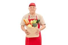 Mature market vendor holding a grocery bag Stock Photos