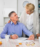 Mature married couple discuss contract  and sign important docum Royalty Free Stock Images