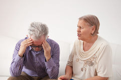 Mature married couple having a conflict at  home. Husband desperately holding his head Royalty Free Stock Photos