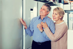Mature married couple in shop of household appliances are choosi Stock Photography