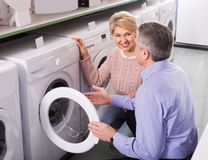 Mature married couple in shop of household appliances. Are choosing home modern washing machine royalty free stock photos