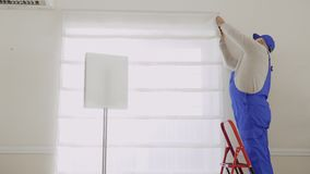 Mature master repair fastening of roller blinds. Mature specialist repair fastening of the standing at the ladder. Old man wearing protective coveralls works as stock footage