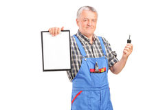 Mature mechanic holding a car key and clipboard Stock Photos