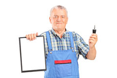 Mature mechanic holding a car key and clipboard Stock Images