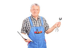 Mature mechanic holding clipboard and a wrench Stock Image
