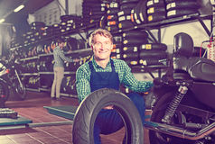 Mature mechanic holding new tyre for motorcycle. In workshop Stock Images