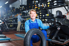 Mature mechanic holding new tyre for motorcycle. In workshop Royalty Free Stock Photos