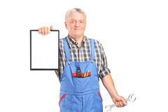 Mature mechanic holding wrench and a clipboard Stock Images